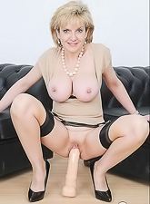 Lady Sonia takes her classy lingerie on the sofa and toys her hungry wet muff