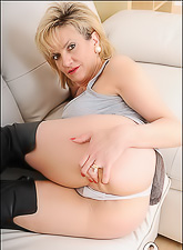 Lady Sonia takes her sexy black high boots on the sofa and fingers her hungry vagina