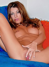 Isabella Camille takes her orange bikini off on the sofa and shows her breasts.