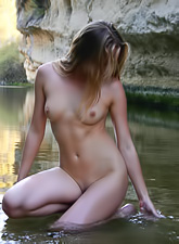 Irina H takes her clothes off by the river and exposes her completely nude body.