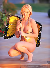 Frisky Alison Angel takes her clothes off and poses as naked butterfly in a park.